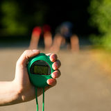 Trainer measuring time of two sprinters. Young couple doing sport outdoors, attempting to run or sprint waiting for the start signal, a trainer is ready to Royalty Free Stock Photos