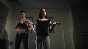 Trainer men are teaching woman lifting dumbbells. In the way they exercise in the gym stock video
