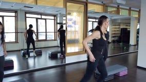 Trainer met haar groep vrouwen die aerobics met speciale banken doen stock videobeelden