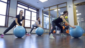 Trainer met haar groep women do exercises met blauwe fitboll in gymnastiek stock video