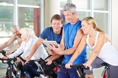 Trainer mit Tablet-PC ältere Gruppe in der Turnhalle trainierend Lizenzfreie Stockfotografie