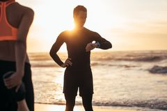 Trainer monitoring progress of a woman exercising at beach. Fitness trainer monitoring progress of a women exercising at beach. Male athlete checking his royalty free stock images