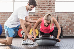 Trainer motivating client doing push ups. In crossfit gym Royalty Free Stock Photo
