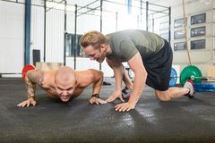 Trainer Motivating Man In Doing Pushups Royalty Free Stock Photos