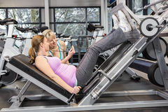 Trainer motivating pregnant woman while using leg press. Trainer motivating pregnant women while using leg press at the gym Royalty Free Stock Photo