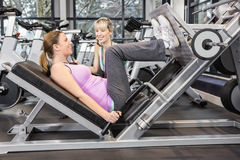 Trainer motivating pregnant woman while using leg press. Trainer motivating pregnant women while using leg press at the gym Stock Images