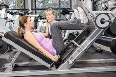 Trainer motivating pregnant woman while using leg press. Trainer motivating pregnant women while using leg press at the gym Stock Photos