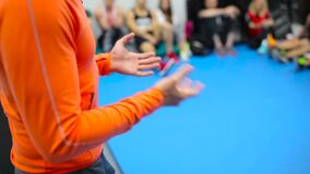 The trainer in orange costume gesticulates hands during the training in the gym. The camera focuses on the man`s hands. The trainer in orange costume standing in stock footage