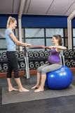 Trainer and pregnant woman using a resistance band Stock Image