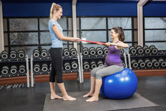 Trainer and pregnant woman using a resistance band Royalty Free Stock Image