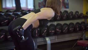 The trainer pumps the muscles of the back and back of the hand in bent position. The fitness trainer in a sports suit pumps the muscles of the back and back of stock video
