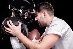 Trainer screaming at boy american football player on black Royalty Free Stock Image