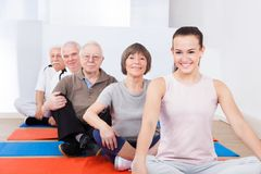 Trainer and senior customers sitting in yoga class Stock Photo