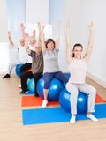 Trainer and senior customers stretching on fitness balls Royalty Free Stock Photo