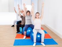 Trainer and senior customers stretching on fitness balls Stock Photo