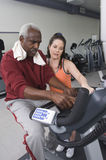 Trainer With Senior Man On Exercise Bike At Gym Stock Photo