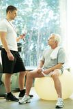 Trainer and senior man in a fitness club stock photos