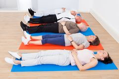 Trainer and senior people lying on exercise mats Royalty Free Stock Photo