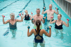 Trainer and senior swimmers exercising in swimming pool Stock Photography
