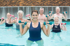 Trainer with senior swimmers exercising in swimming pool Stock Photo