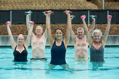 Trainer and senior swimmers lifting dumbbells in swimming pool. Portrait of trainer and senior swimmers lifting dumbbells in swimming pool Royalty Free Stock Images