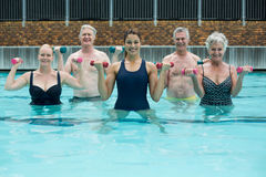 Trainer and senior swimmers weightlifting in swimming pool Stock Image