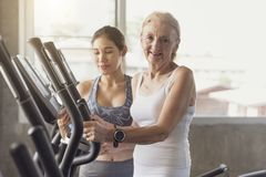 Trainer with senior woman exercising spinning bike in fitness. Trainer with senior women exercising spinning bike in fitness gym. elderly healthy lifestyle royalty free stock images