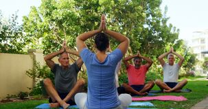 Trainer and seniors performing yoga in garden 4k