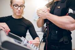 Trainer setting up ems device. Front portrait of trainer setting up ems device for sportsman Stock Photos