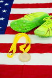 Trainer shoes and gold medal on american flag Royalty Free Stock Photo