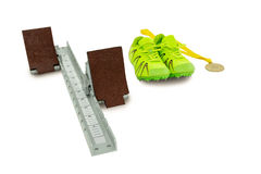 Trainer shoes, starting block and gold medal on white background Stock Photography