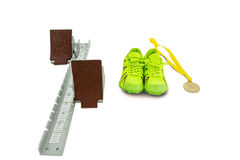 Trainer shoes, starting block and gold medal on white background Stock Photo