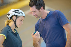 Trainer showing cyclist time Royalty Free Stock Image