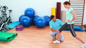 Trainer showing his client how to lunge correctly. At the rehabilitation center stock footage