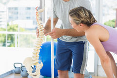 Trainer showing model of spinal cord to woman Royalty Free Stock Photos
