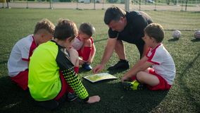 Trainer is showing plan of football field to little boys footballers. Sitting on gass stock video footage