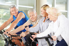Trainer showing stopwatch to senior group in gym Stock Photography