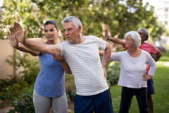 Trainer showing stretching exercise to senior people. Trainer showing senior people stretching exercise at park Stock Photography