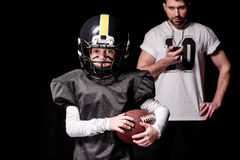 Trainer with sport timer looking at boy american football player. On black Stock Image