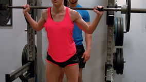 Trainer spotting woman lifting weight. In ultra hd format stock footage