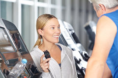 Trainer with stopwatch in a fitness Stock Photos