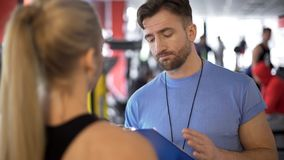 Trainer supervising client workout program and giving useful advice on training stock image
