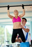 Trainer support young woman while lifting on bar in fitness gym Royalty Free Stock Photography