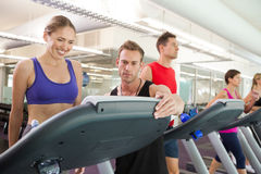 Trainer talking to his client on the treadmill Stock Photo