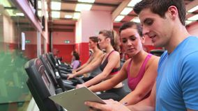Trainer talking to woman on exercise bike stock footage