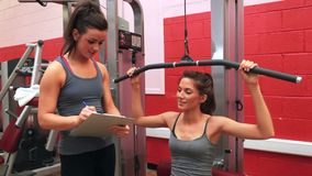 Trainer talking to woman on weights machine. In gym stock video