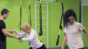 Trainer training elderly woman in the gym. Trainer teaches elderly woman to squat correctly with belts. Grandmother with granddaughter makes a sport exercises stock video footage