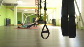 The trainer teaches in the gym to practice a man on the hinges of the TRX while performing an exercise facial thrust