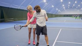 Trainer teaches man to play tennis. Handsome adult caucasian man learns to play tennis. Woman-trainer shows the player how to stand and holds racquet correctly stock video