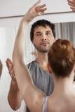 Trainer Teaching Ballet To Female Dancer In Studio. Mid adult male trainer teaching ballet to female dancer in studio Stock Photo